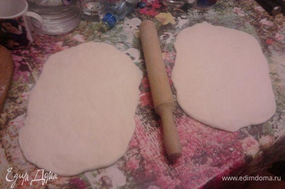 Когда тесто подойдет во второй раз, обмять его и разделить на 2 части. Раскатать.