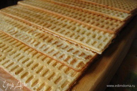Вафельницу слегка смазать маслом и испечь одну за другой вафли (каждая вафля - это приблизительно 2 ст.ложки теста). Готовым вафлям дать остыть.