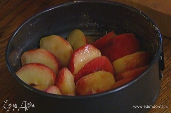 Персики, удалив косточки, разрезать на 6 частей и уложить на дно формы срезами вниз как можно плотнее друг к другу.