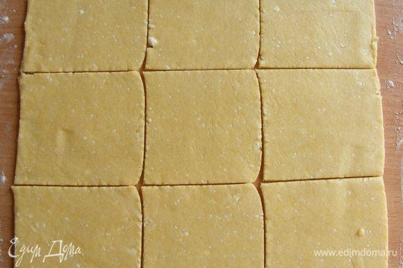 Тесто раскатать на присыпанной мукой поверхности. Нарезать на квадратики.