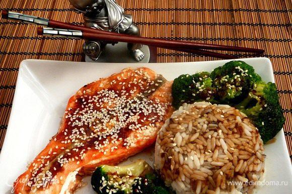 Выложить на тарелку рыбу, брокколи и рис. Полить соусом, посыпать кунжутом.