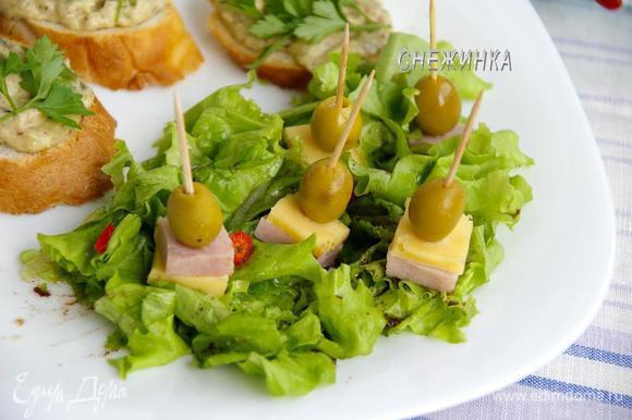 Делаем канапе из ветчины, сыра и оливок. Устанавливаем на листья салата.
