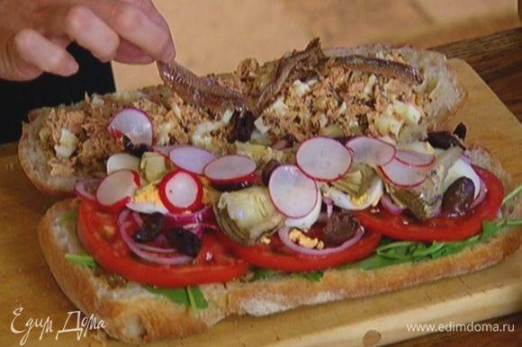 Выложить начинку из тунца на вторую половину хлеба, сверху поместить анчоусы.
