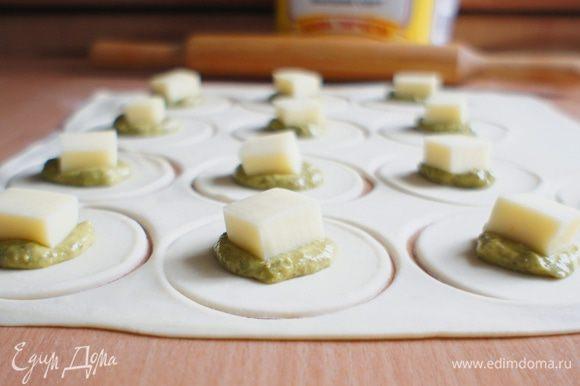На каждый кружочек теста положить по 1 ч.л. песто и кусочек сыра.