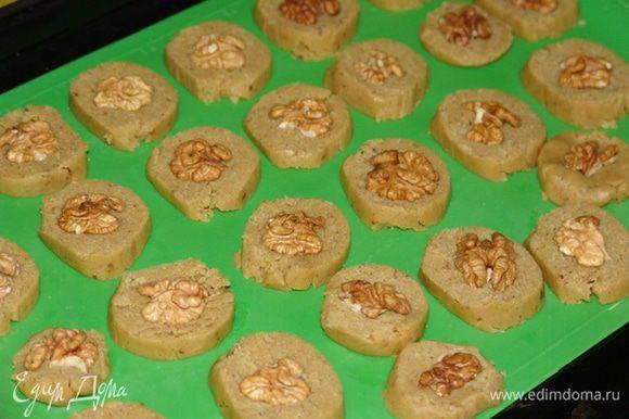 Нарезаем колбаски теста на кусочки толщиной 0.5 см, хорошо вдавливаем по половинке ореха. Выпекаем в разогретой до 180 градусов духовке около 15-20 минут.