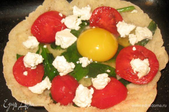 На помидоры разбиваем яйцо, сверху выкладываем кусочки феты (брынзы). Противень ставим в разогретую до 180 градусов духовку. Запекаем, пока яйцо не загустеет (или до любимого состояния яйца).