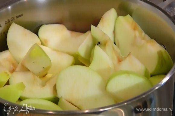 В небольшой кастрюле соединить 150 г сахара и 100 г сливочного масла, добавить яблоки и прогревать на огне до полного растворения сахара. Периодически помешивать деревянной ложкой, так чтобы все яблоки пропитались карамельным соусом.