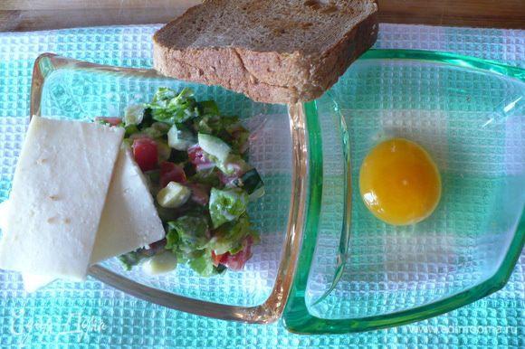 Хлеб подсушить в тостере. Мелкими кубиками нарезать огурчик, помидорку и листья салата. Овощи смешать с соусом «цезарь».