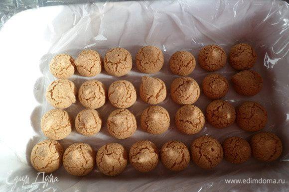 Берем форму, покрываем дно пищевой пленкой , укладываем миндальные печенюшки