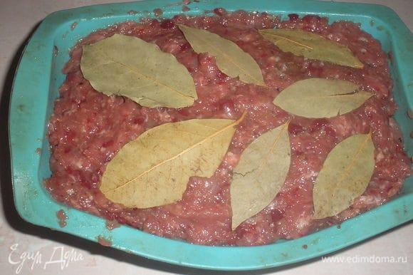 Через указанное время фарш вынимаем из холодильника, добавляем яйцо, перемешиваем. Выкладываем фарш в прямоугольную форму. Сверху выкладываем несколько листочков лаврового листа.