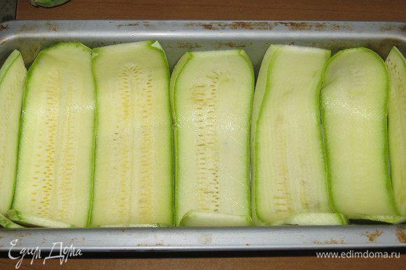 Форму для запекания смазать оливковым маслом и выложить дно пластинками цукини.