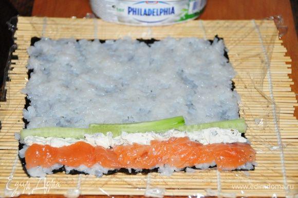 Первый ролл – Футомаки с форелью: На нори руками выкладываем тонкий слой риса, тщательно разравниваем. Руки постоянно смачиваем в уксусе, т.к. рис очень липкий! С краю, который ближе к Вам выкладываем начинку: кусочки рыбы, рядом с ней полосочку сыра «Филадельфия», огурчик. Можно добавить маленькие капельки васаби.