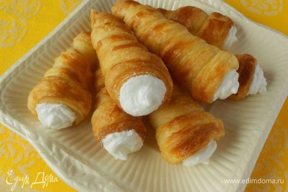 Сложить белковый крем в кондитерский мешок и наполнить трубочки.На крем нанести посыпку. Трубочки выложить на блюдо и присыпать сахарной пудрой через ситечко. Подавать сразу же.