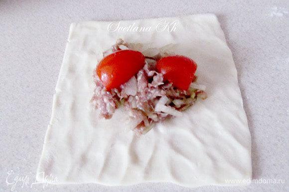 Готовый квадратик теста размять таким образом, чтобы серединка осталась толстой, а края были тоньше. Выложить в центр фарш и разрезанный помидор.