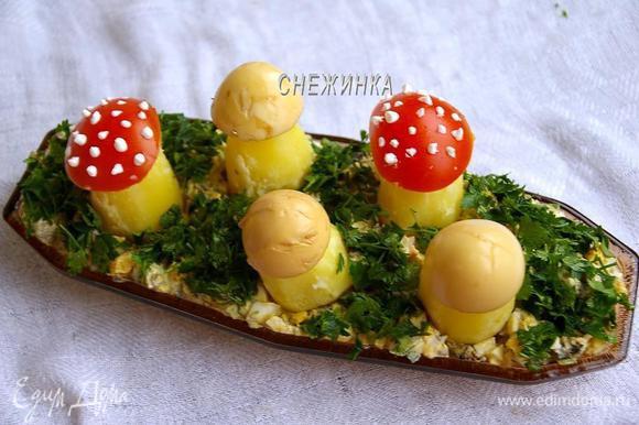 Салат распределяем на блюде. Укладываем на него «грибочки», а между ними посыпаем измельчённой петрушкой (или укропом).