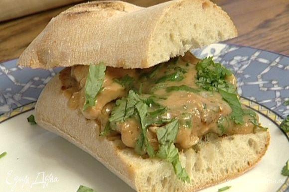 На одну половину хлеба выложить курицу, полить получившимся соусом, посыпать зеленью кинзы, накрыть второй половиной хлеба.