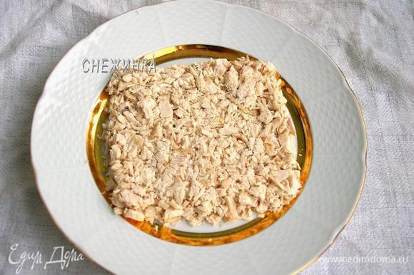 Курицу мелко нарезаем. Укладываем половину курицы на блюдо в виде квадрата. Хорошо утрамбовываем.