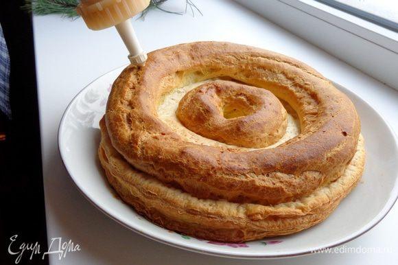 Когда основа торта полностью охладится, начать сборку. Наполнить кондитерский мешок кремом 1, с помощью тонкой насадки сделать отверстия в заварных кругах и наполнить их кремом.