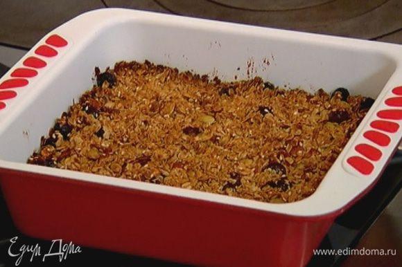 В форму для выпечки выложить хлопья с медом и сухофруктами, разровнять и отправить в разогретую духовку на 30–40 минут.