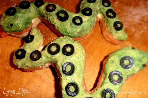 Колечки оливок укладываем на спинки змеек.