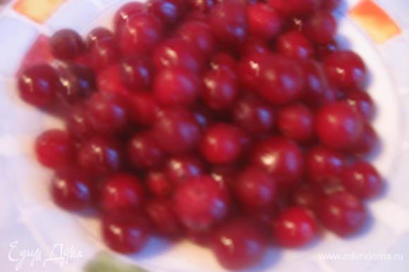 Приготовьте из клюквы и сахара соус Сполосните ягоды и выложите их в кастрюлю или сковородку, в которой будете готовить соус . Замороженные ягоды размораживать не нужно. Апельсин хорошо помыть. Натрите цедру и добавьте ее к ягодам. Выдавите сок из апельсина и тоже добавьте в посуду. Добавьте воду и коньяк. Дайте смеси прокипеть на слабом огне 5-10 минут.