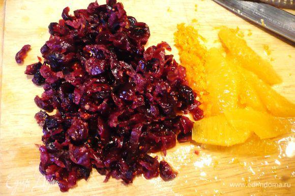 Ставим вариться рис. Бруснику мелко нарезаем, с половинки апельсина снимаем цедру, щедро срезаем корки и освобождаем от пленок мякоть, нарезаем дольки апельсина.