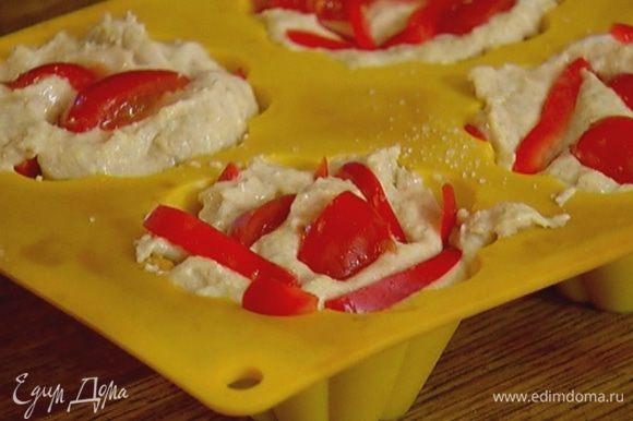 На дно силиконовых формочек для маффинов выложить часть нарезанных помидоров и перца, присыпать щепоткой сахара и разложить тесто. Сверху выложить оставшиеся помидоры и перец.