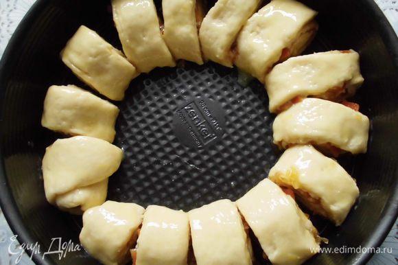 Аккуратно свернуть тесто в рулет и нарезать его на 14 кусочков. Форму (у меня 26 см, но можно и 24) смазать растительным маслом и выложить кольцом рулетики. Смазать их желтком буквально с каплей молока и выпекать 30-40 минут.
