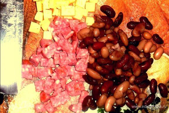 Сыр, колбасу нарезаем кубиками. Мелко нарезаем зелень