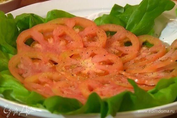 На блюдо выложить листья салата, помидоры, посолить, поперчить.