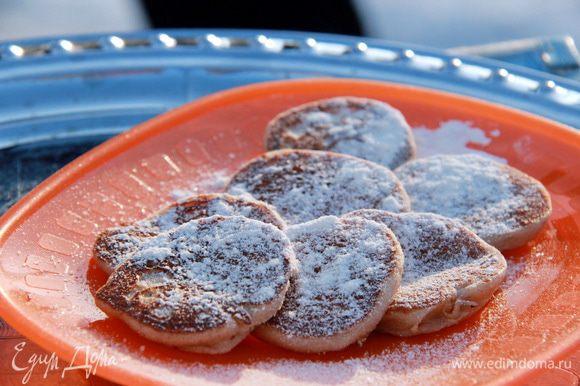 Выложить на тарелку, обильно посыпать сахарной пудрой. Подавать тёплыми с ароматным и уютным сливочным маслом.
