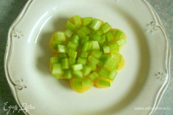 На 4 тарелках выложить ломтики картофеля в один слой, формируя полный круг. Сверху распределить кусочки сельдерея, поверх него по щедрой ложке соуса.