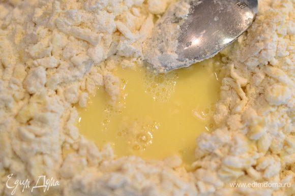 Сделать углубление в тесте и добавлять частями яичную смесь,перемешивая все ложкой.