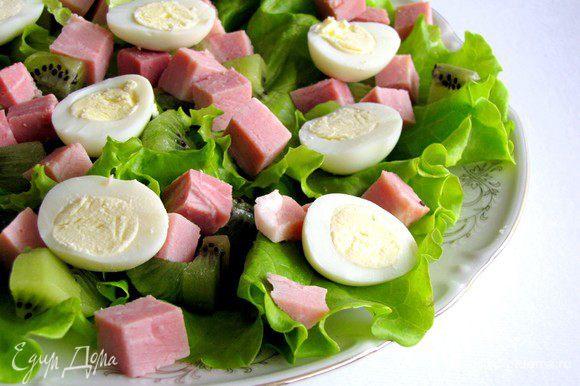 Перепелиные яйца разрезать на половинки и выложить на блюдо.