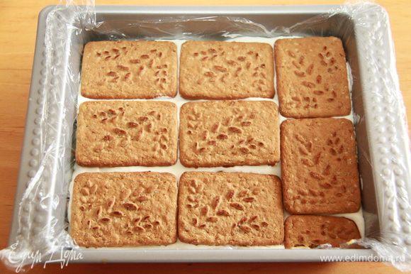 Манго покрываем оставшимся кремом, выкладываем слой печенья. Убираем заготовку в морозилку на полчаса.