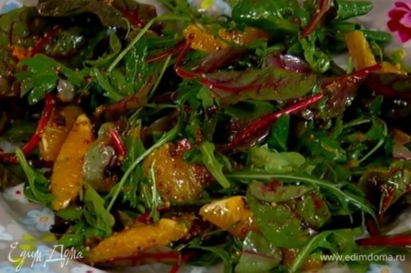 Полить салатные листья с апельсином заправкой, перемешать и выложить на тарелки.