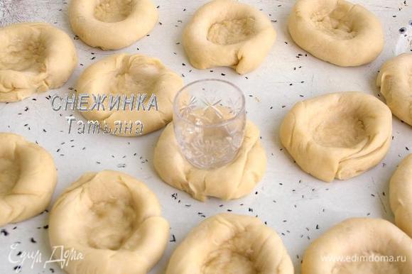 Подошедшее тесто раскатываем в толстый жгут и делим на 13 равных частей. Из каждой части скатываем круглую булочку и укладываем на смазанный маслом противень. Оставляем подняться на 10 минут. Затем с помощью донышка рюмки делаем в каждой булочке углубление в центре. Если тесто будет прилипать, можно немного смазать его в масле.