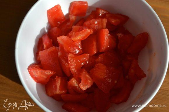На кожице помидора сделать крестообразный надрез, залить его на пару минут кипятком и очистить от кожуры. Очистить помидор от семян и нарезать на небольшие кусочки.