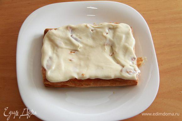 Сборка торта. Слегка прижмите нижний корж, чтобы он немного осел. Намажьте 1/4 объёма крема на корж.