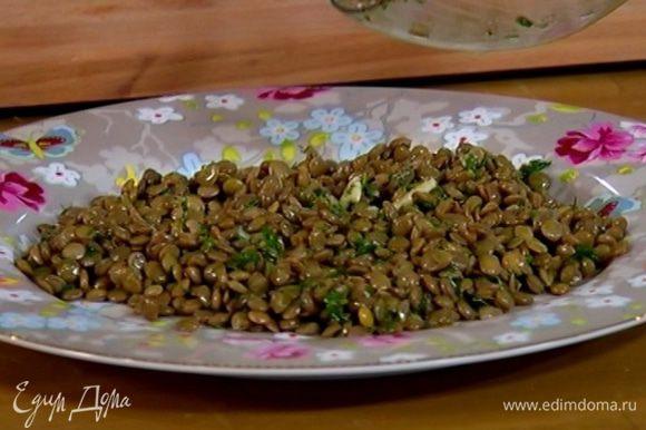 В теплую чечевицу добавить 3/4 всей заправки, перемешать и выложить на большую тарелку.
