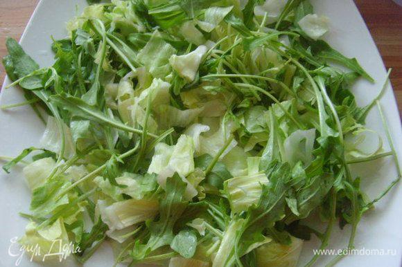 На блюдо выложить салатные листья, полить половиной заправки.