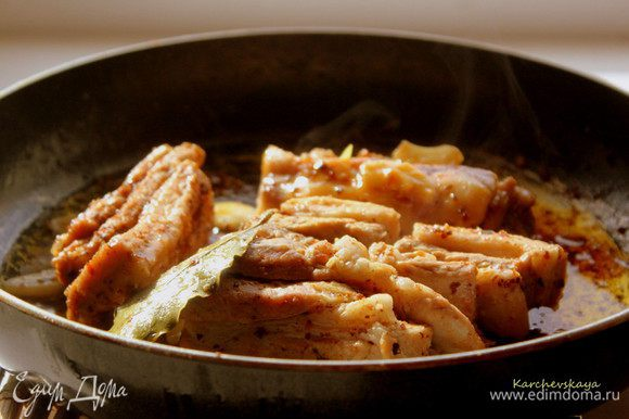 Через 2 часа достать мясо из маринада. В сковороде обжарить на оливковом или растительном масле ребра до золотистой корочки. Затем влить мясной бульон (или горячую воду), положить лавровый лист и тушить на медленном огне 30-40 минут до готовности.