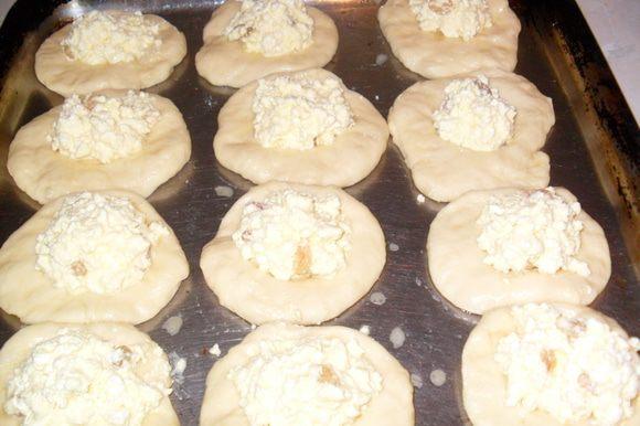 приготовление теста: В тёплое молоко добавить 1 ст.л. сахара и дрожжи, оставить на несколько минут пока дрожжи растворятся и чуть поднимутся. В муке сделать лунку туда добавить яйцо, масло (растопленное и чуть тёплое) добавить оставшийся сахар, соль всё перемешать, добавить поднявшиеся дрожжи. Замесить тесто и оставить на 1 час. приготовление начинки: В творог добавить желтки, сметану, сахар, изюм Всё хорошо перемешать. Из теста скатать шарики размером с куриное яйцо и дать им в течении нескольких минут подойти. Из шариков сделать небольшие лепёшки, затем дно стакана обмакнуть в муку и сделать в лепёшках углубление. Выложить лепёшки на противень, смазать взбитым яйцом с молоком и начинить творогом. Выпекать при 180 градусах в духовке около 30 мин.