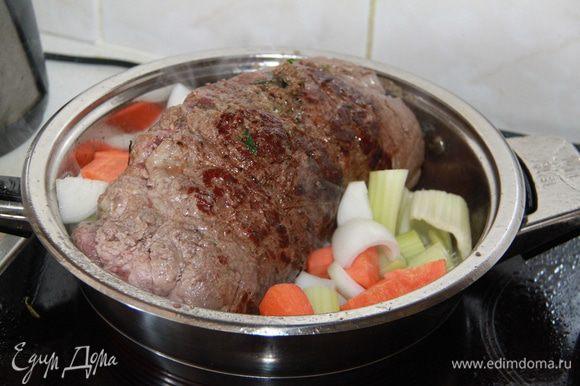 Обжарить рулет до румяной корочки. Нарезать лук, сельдерей и морковь крупными кусками и добавить овощи в кастрюлю, обжарить.