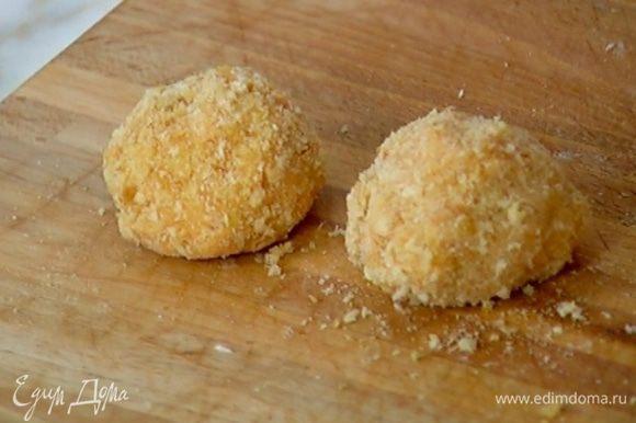Сформировать из куриной массы шарики, обвалять их в хлебных крошках, затем обмакнуть в яйцо и еще раз обвалять в сухарях.