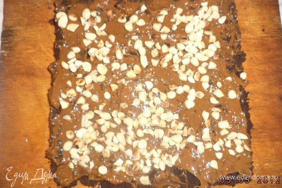 Нижний корж смазать сгущёнкой, посыпать половиной орехов. Накрыть вторым коржом.