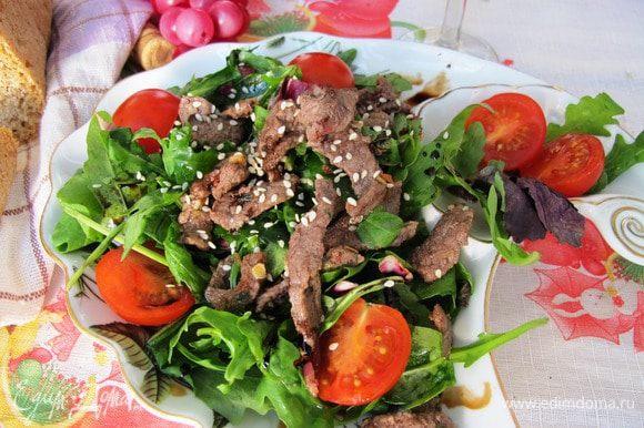 Сервируем салат порционно. Выкладываем салатные листья, сверху мясо, помидорки черри.Поливаем мясным соком, выделившимся при жарении, сбрызгиваем бальзамиком и посыпаем кунжутом.
