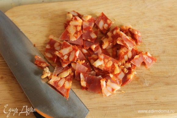 Колбасу нарезать мелкими кубиками. Добавить в подошедшее тесто и хорошо ее вмешать.