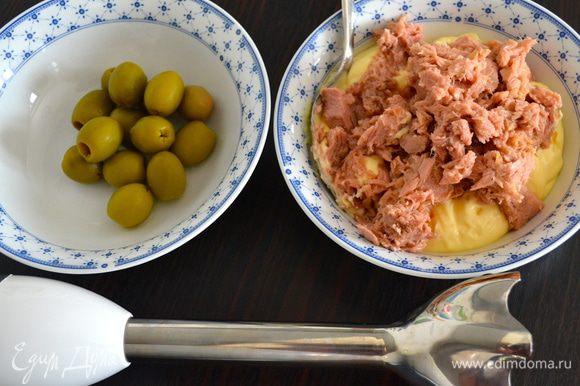 Тунца достать из банки, дать стечь лишней жидкости, поломать вилкой. С помощью погруженного блендера (или в миксере) измельчить тунца с майонезом, кетчупом, оливками (отложите одну для украшения), добавив чуть-чуть оливкового масла.