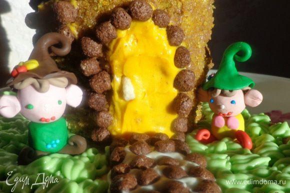 Смазать основу домика коричневым кремом, обсыпать его желтой присыпкой и охладить. Затем аккуратно ножиком нарисовать дверь и окно, выскоблить коричневый крем и заполнить поверхности желтым кремом. По краю положить кукурузные шарики. На двери сделать ручку.